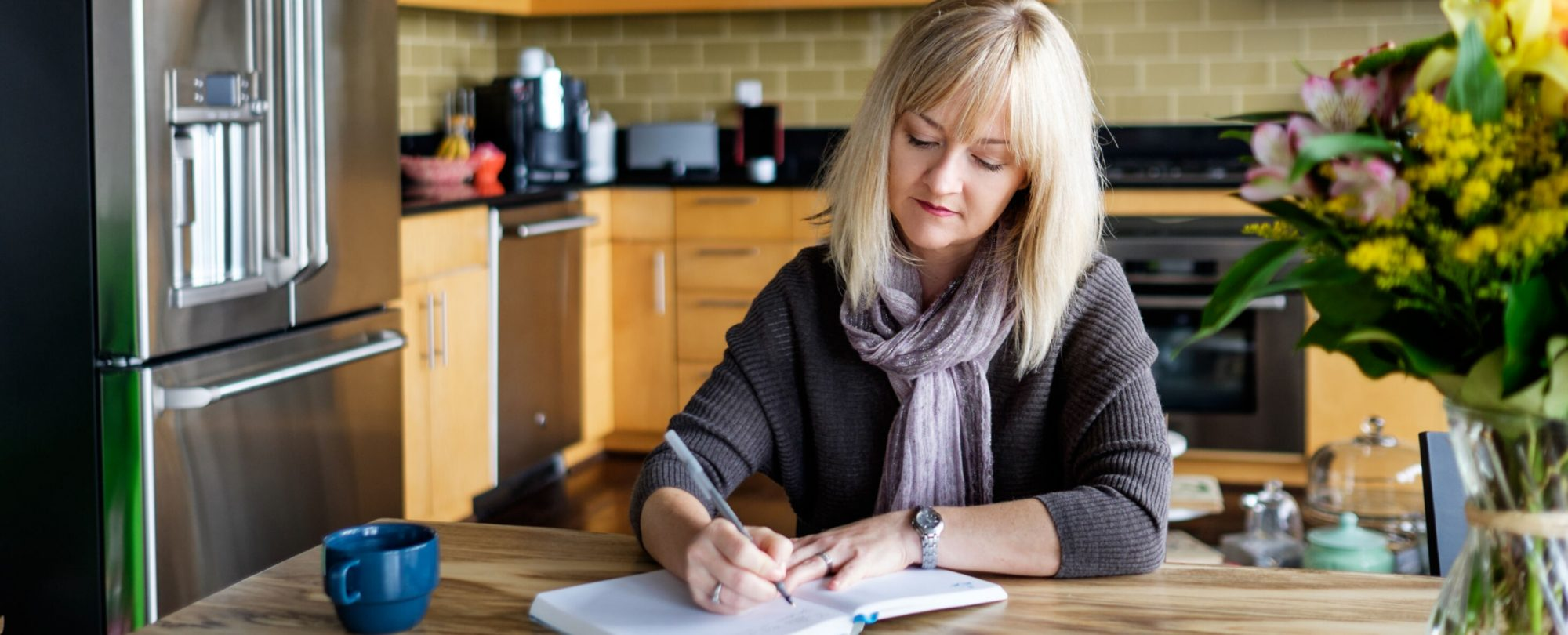 Woman Writing On A Notebook At Home